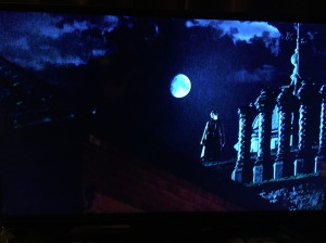 A screengrab of Sherlock Holmes standing on a roof, in the rain, wirh a mostly full moon behind him.